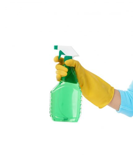 Unrecognizable housemaid wearing rubber gloves holding spray cleaner in hand while standing against white background, copy space